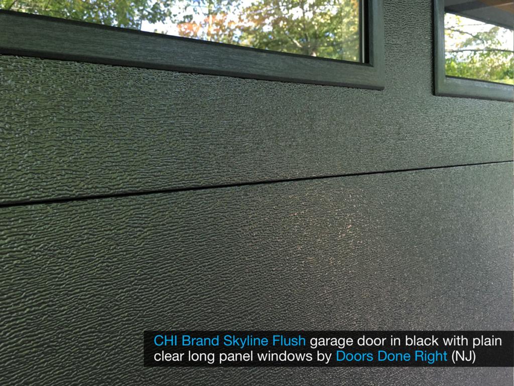 chi model 2284 skyline flush garage door in black with clear long panel windows in top door section - wood grain closeup