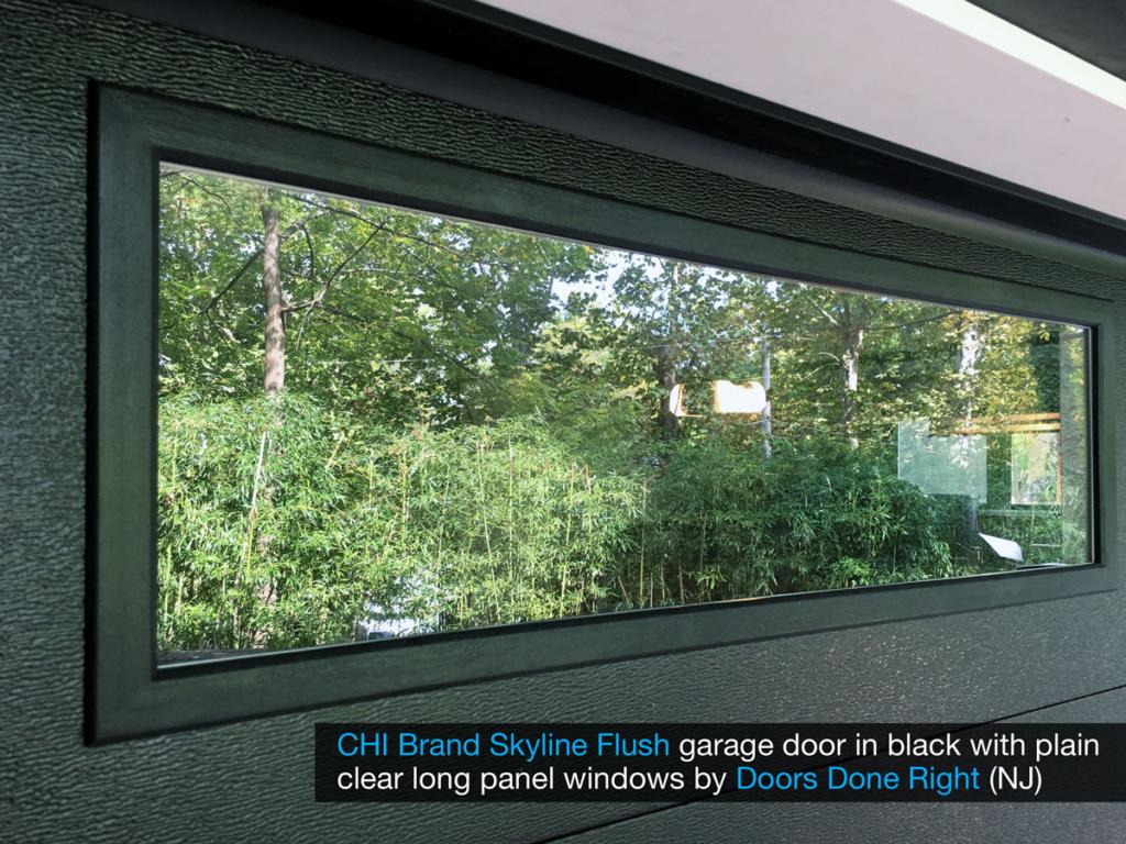 chi model 2284 skyline flush garage door in black with clear long panel windows in top door section - window closeup